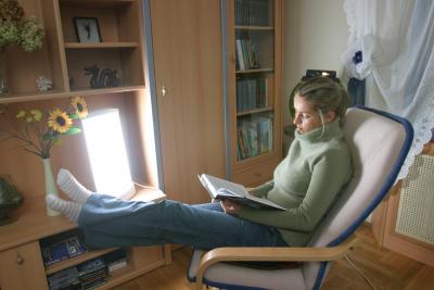 Depresja zimowa - fototerapia - kobieta siedząca wfotelu iczytająca książkę przy świetle lampy