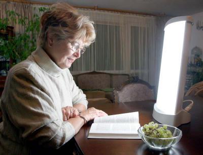kobieta czytająca książkę przy stole